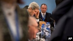 U.S. Secretary of State John Kerry, center, waits for the start of a round table meeting of the NATO-Ukraine Commission at NATO headquarters in Brussels Dec. 2, 2014.