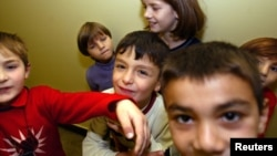 FILE - Chechen children play at a refugee centre in Moszno, near Poland's capital Warsaw, Sept. 20, 2004. Poland could start educating children of refugees at the centers where they live rather than in public schools under a plan, the government says, Feb. 26, 2018.