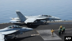 Sailors direct F/A-18E fighter jets on the flight deck of the USS George H.W. Bush aircraft carrier. This is a U.S. Navy photo obtained on Aug. 8, 2014.