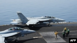Sailors direct F/A-18E fighter jets on the flight deck of the USS George H.W. Bush aircraft carrier in this recent U.S. Navy handout photo obtained Aug. 8, 2014.