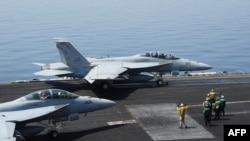2014年8月8日美国海军水兵在乔治布什航空母舰上指挥执行任务的超级大黄蜂式打击战斗机