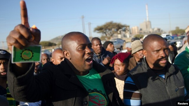 Mineworkers dance as they gather for check-ins near Lonmin's Marikana platinum mine before returning to work, June 25, 2014.
