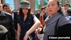 汪姓女青年在手铐打开一只后戴着手铐跟围观路人在一起。(网络图片)
