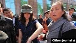 武汉市一位汪姓女青年在手铐打开一只后戴着手铐跟围观路人在一起。她被誉为学雷锋的女孩,2013年为救人助人,向执勤民警求助无果后,因用脚踢警车来宣泄愤怒而遭警察以手铐铐住(网络图片)