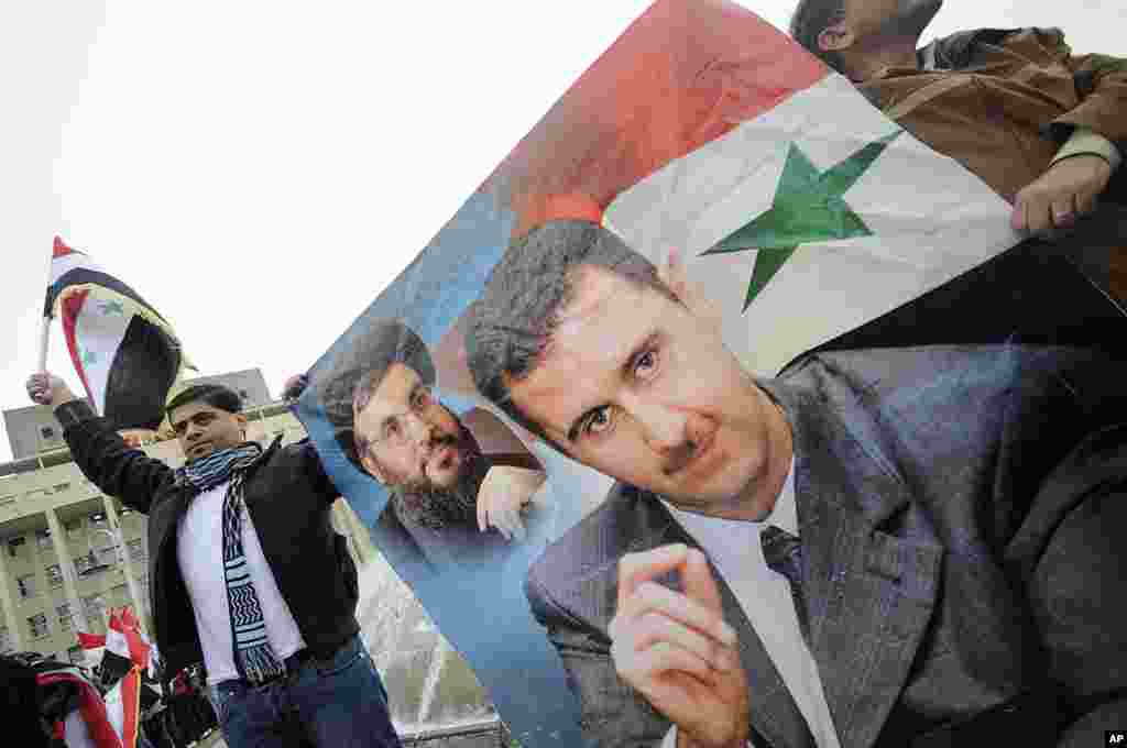 People wave Syrian flags and carry a poster depicting Syria's President Bashar al-Assad and Lebanon's Hezbollah Leader Sayyed Hassan Nasrallah during a rally to show support for al-Assad in Damascus, Syria, November 16, 2011. (Reuters)
