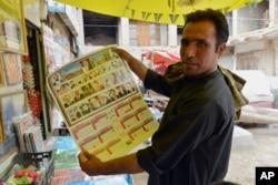ເຈົ້າຂອງຮ້ານຄ້າ ຊາວອັຟການິສຖານ ຄົນໜຶ່ງ ສະແດງໃຫ້ເຫັນ ເຖິງປະຕິທິນ ທີ່ມີພາບຂອງບັນດາຜູ້ນຳ ທາລີບານ ລວມທັງ Mullah Mohammad Omar ຢູ່ທີ່ເມືອງ Kandarhar ທາງທິດໃຕ້ຂອງນະຄອນຫຼວງ ກາບູລ ປະເທດອັຟການິສຖານ, ວັນທີ 30 ກໍລະກົດ 2015.
