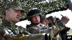 Ukrainian President Petro Poroshenko, left, watches a military exercise of the Ukrainian armed forces in Mykolaiv region, April 25, 2015.