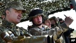 ປະທານາທິບໍດີ ຢູເຄຣນ ທ່ານ Petro Poroshenko (ຊ້າຍ) ເບິ່ງ ການຊ້ອມລົບ ຂອງກອງທັບຢູເຄຣນ ຢູ່ໃນຂົງເຂດ Mykolaiv ຂອງ ຢູເຄຣນ, ວັນທີ 25 ເມສາ 2015.