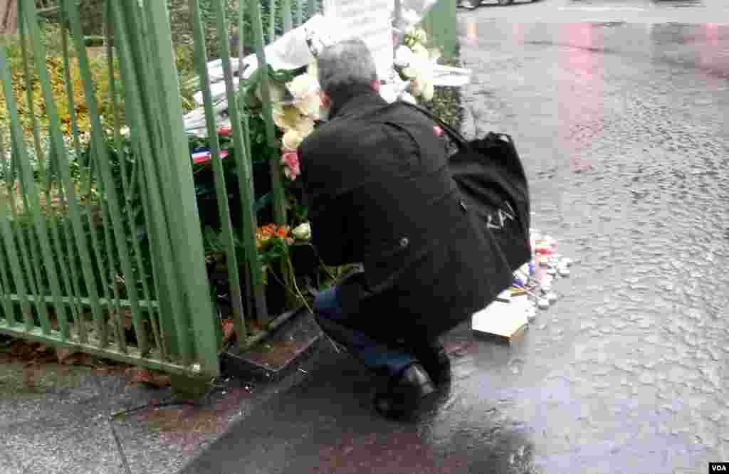 A man kneels by a plaque near Cafe Bonne Biere where jihadists killed 5 people last year, in Paris, Nov. 13, 2016. (L. Bryant/VOA)