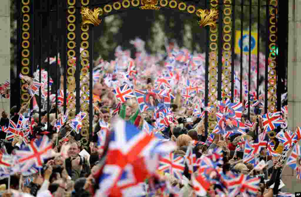 People wave British flags outside Buckingham Palace during the wedding. (Reuters/Dylan Martinez)