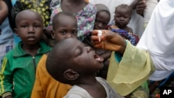 FILE - A health official administers a polio vaccine to children at a camp for people displaced by Islamist Extremist in Maiduguri, Nigeria, Aug. 28, 2016.