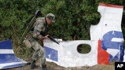Proruski pobunjenik kod delova olupine aviona Malezija Erlajnza na polju u istočnoj Ukrajini, 9. septembra 2014.