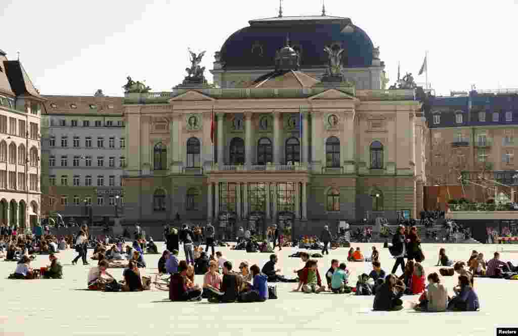 People enjoy the sunny weather as they sit on the Sechselaeutenplatz Square in front of the opera house in Zurich, Switzerland.