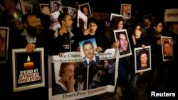 Israelis hold placards depicting people who were killed in pro-Palestinian attacks during a protest against the release of Palestinian prisoners, outside Israel's Prime Minister Benjamin Netanyahu's residence in Jerusalem, Mar. 26, 2014.