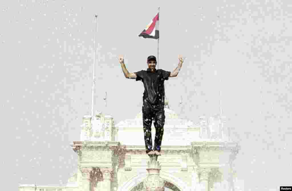 Một người biểu tình đứng trên đài phun nước trước Dinh Qubba tại Cairo, Ai Cập. Hàng ngàn người ủng hộ Tổng thống Hồi giáo Mohamed Morsi bị lật đổ đã biểu tình ở thủ đô Cairo và Alexandria, thành phố lớn thứ hai, cùng những thành phố ven biển và ở vùng châu thổ sông Nile khác.