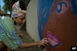 "Graffiti artist Maiara Viana Rodrigues paints a mural at her home neighborhood in Rio de Janeiro, Brazil, March 7, 2017. ""We use graffiti to end violence against women,"" says the 25-year-old designer and visual artist."