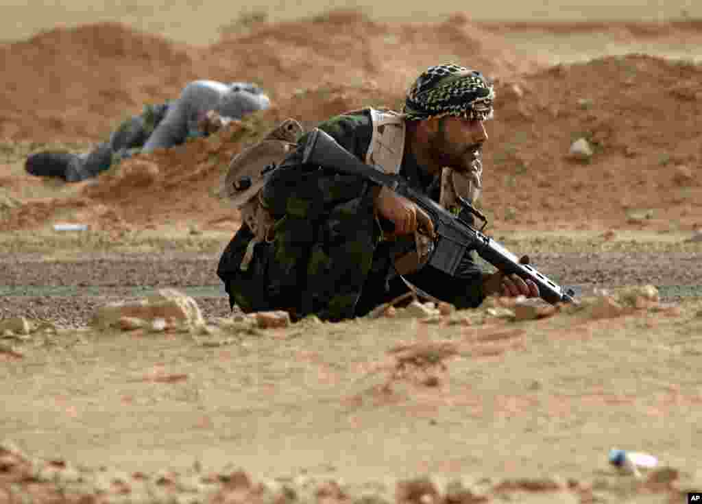 A rebel fighter takes cover from shelling by soldiers loyal to Libyan leader Moammar Gadhafi during a battle near Ras Lanuf, March 04, 2011. (Reuters Image)
