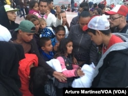 Recibiendo instrucciones y cobijas para pasar la noche en la frontera. (A. Martínez/VOA).