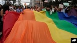Para peserta pawai memamerkan bendera pelangi besar saat mengikuti pawai LGBT, Gay Pride Parade, di Quito, Ekuador, Sabtu, 29 Juni 2019. (Foto: AP)