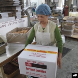 A Tsue Chong factory worker prepares to ship out a box of fortune cookies.