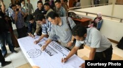 Para dosen dan mahasiswa UNS Solo menggalang tanda tangan mendukung penolakan revisi UU KPK, di kampus UNS Solo, Rabu (11/9). (Foto: Humas UNS Solo)