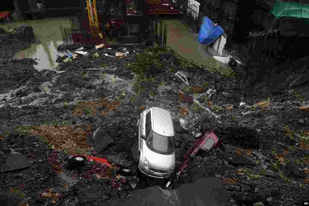 Cars lie buried in debris after the wall of a building under construction collapsed during heavy rains in Mumbai, India.