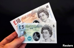 Sample polymer five and ten GB pound banknotes are displayed at the Bank of England in London, Sept. 10, 2013.