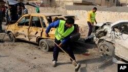 Para pekerja pemerintah daerah setempat tengah membersihkan lokasi serangan bom di dekat Universitas teknologi di jalan Sina, pusat kota Baghdad (15/1).