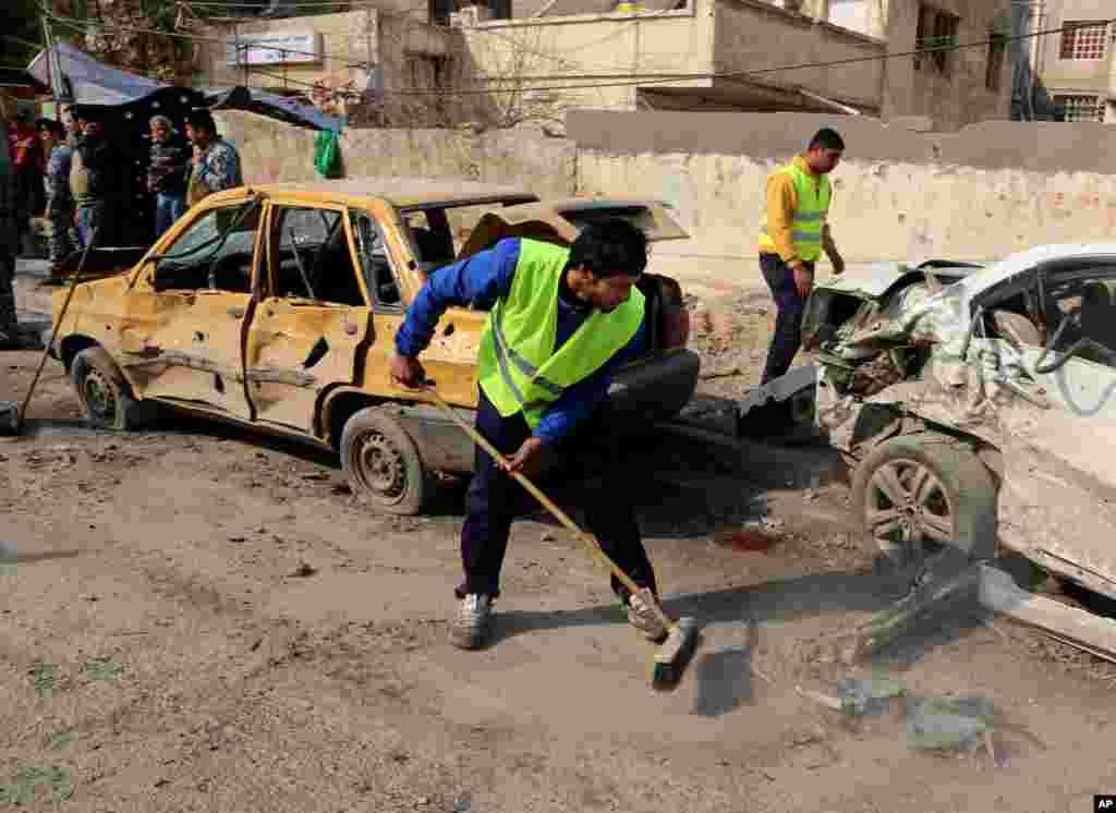 Municipality workers clean up after a car bomb attack near the Technology University on Sinaa Street in downtown Baghdad, Jan. 15, 2014.