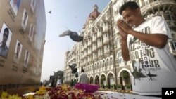 A man pays homage in front of portraits of police officers killed in the Mumbai terror attacks outside the Taj Mahal Palace hotel on Nov. 26, 2010, the second anniversary of the attacks.