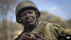 "A Kenyan army soldier wears a helmet on which is written in Kiswahili ""Tea in Kismayo"", referring to a key strategic Somali town then under the control of al-Shabab, checks his ammunition belt near the town of Dhobley, in Somalia."