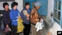 Ảnh do Chương trình Thực phẩm Thế giới của LHQ công bố cho thấy phụ nữ Bắc Triều Tiên xếp hàng chờ nhận ngô tại một trung tâm phân phối công cộng ở quận Phyongwon, phía nam thủ đô Bình Nhưỡng