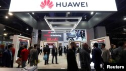 FILE - Attendees pass by a Huawei booth during the 2019 CES in Las Vegas, Jan. 9, 2019.