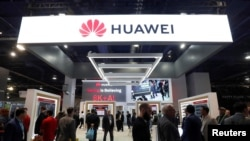 FILE - Attendees pass by a Huawei booth during the 2019 CES in Las Vegas, Nevada, Jan. 9, 2019.