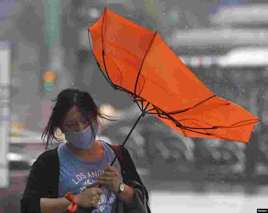 A woman holds her umbrella while walking against strong winds as Typhoon Matmo hits Taipei, July 23, 2014.