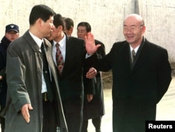 FILE - Former South Korean president Chun Doo-hwan, right, waves goodbye as he is escorted by a secret service agent outside the walls of Anyang Prison to a waiting car shortly after being released from the jail on a special pardon in Anyang, Dec. 22, 199