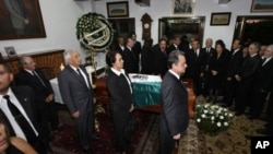Relatives, friends and Mexican politicians surround the coffin, covered by a Mexican flag, containing the body of Mexico's former President Miguel de la Madrid during his wake in Mexico City, Sunday April 1, 2012.