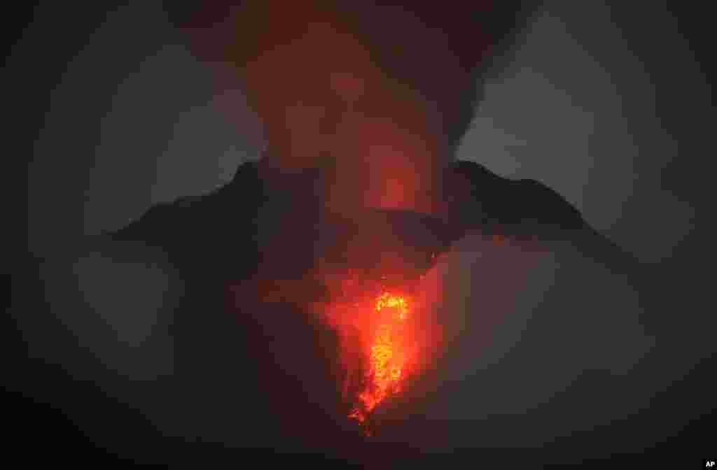 Gunung Sinabung memuntahkan lava dan gas vulkanik terlihat dari Desa Jeraya, Kabupaten Karo, Sumatra Utara.