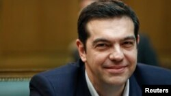 Greek Prime Minister Alexis Tsipras smiles as he attends the first meeting of the new cabinet in the parliament building in Athens, Jan. 28, 2015.