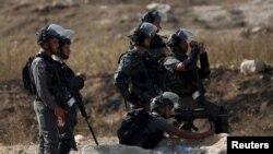 Seorang polisi perbatasan Israel membidik senjatanya ke warga Palestina dalam bentrokan dengan warga Palestina di titik pemeriksaan Hawara, Israel dekat kota Tepi Barat Nablus, 16 Oktober 2015. (REUTERS/Ahmad Talat)
