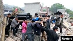 Dân chúng khiêng quan tài nạn nhân đi qua đống đổ nát sau trận động đất mạnh tại huyện Lô Sơn, tỉnh Tứ Xuyên, ngày 21/4/2013.
