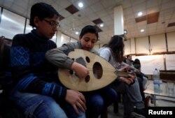 Seorang anak laki-laki memainkan alat musik oud di Institut Paduan Suara Nasional di Aleppo, Suriah, 9 Februari 2018.
