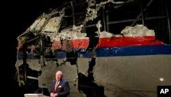 荷兰安全委员会主席尤斯特拉站在被击落坠毁的马航MH-17航班得到重组的机身前发布该委员会的报告。 (2015年10月13日)