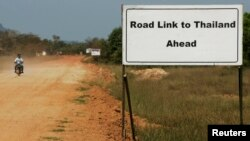 FILE - A sign showing the road leading to Thailand is seen near Dawei in southern Myanmar, close to the site of a planned special economic zone and deep sea port, Nov. 19, 2011.