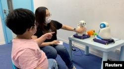 Sarah Ng, seorang tutor, menggunakan robot untuk mengajar anak berkebutuhan khusus cara memperkenalkan diri, di Hong Kong, China, 17 April 2021. (Foto: Yoyo Chow/Reuters)
