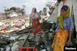 انڈونیشیا میں زلزلے سے بڑے پیمانے کی تباہی کے بعد خواتین اپنے گھروں میں بچ جانے والی چیزیں ڈھونڈ رہی ہے۔ 2010