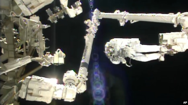 In this image made from video provided by NASA, Italian astronaut Luca Parmitano stands on the end of a robotic arm during a spacewalk outside the International Space Station, July 9, 2013.