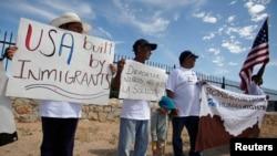ARCHIVO - Residentes de la frontera mexicana y miembros de la Red Fronteriza de Derechos Humanos (BNHR) sostienen carteles y pancartas durante una protesta contra la militarización fronteriza y la deportación de niños, frente a un centro de detención en El Paso, Texas, el 24 de agosto de 2017.