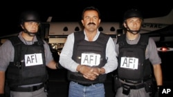 Mexican authorities escort accused drug cartel leader Caro-Quintero, Dec. 20, 2001, at an airport in Sinaloa, Mexico.