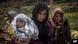 یونان پہنچنے والی پناہ گزین عورتیں بچے سڑک پر کھڑے ہیں۔ (فائل فوٹو)
